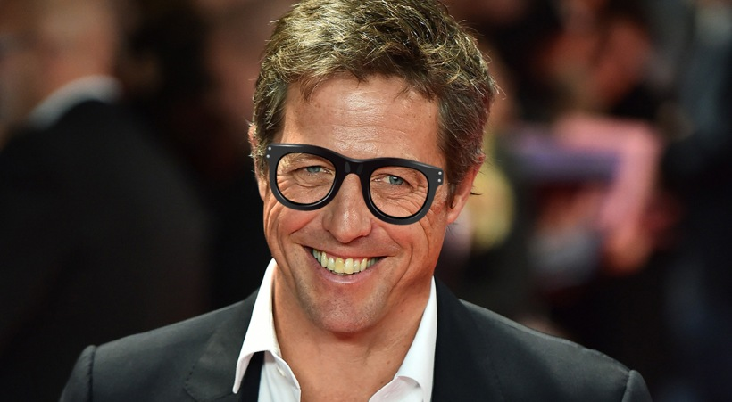British actor Hugh Grant poses for pictures on the red carpet as he arrives to attend the European premier of his latest film